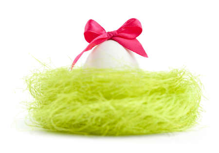 chucky: Egg with pink bow is in the nest of sisal filler, isolated on white