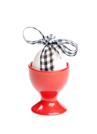 chucky: Easter egg with checked ribbon is in red egg cup, isolated on white. Traditional symbol of the feast