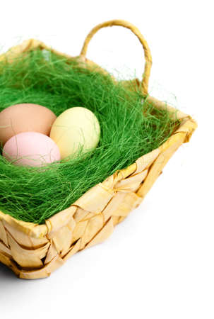 Colored easter eggs are in braided basket with sisal green fibre, isolated on white Stock Photo - 18042215
