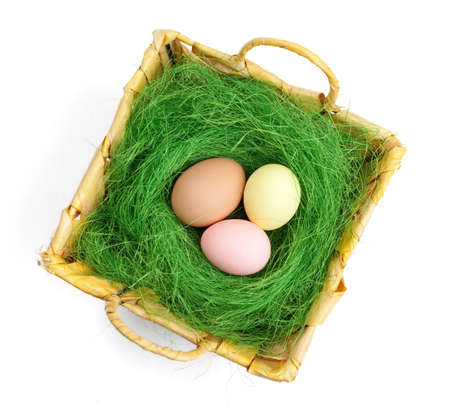 Colored easter eggs are in wattled basket with sisal green fibre, isolated on white Stock Photo - 18042259