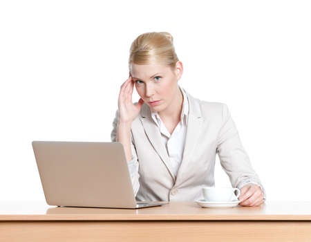 seriously: Young businesswoman sitting at a office table with laptop, isolated Stock Photo