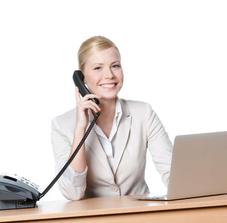 Young businesswoman sitting at a desk and talking by phone, isolated photo