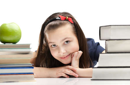 Schoolgirl peeps out through the books, isolated, white background photo
