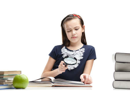 Little schoolgirl wonders about interesting material in the book, isolated, white background photo