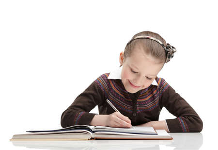 Pupil writes something at her copybook, isolated, white background photo