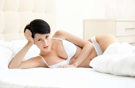 Woman in bra is lying in the queensize bed photo