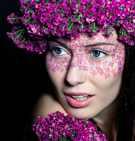 Close-up portrait of young beautiful blue-eyed woman with flowered wreath and fashionable makeup photo