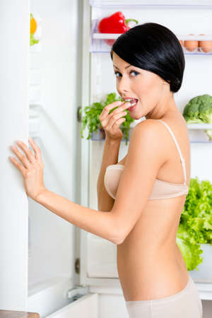 Woman eating near the opened refrigerator full of vegetables and fruit. Concept of healthy and dieting food Stock Photo - 18077255