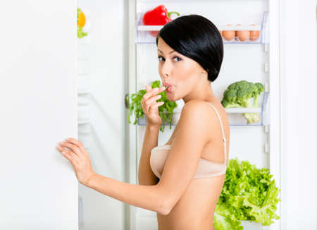 Girl eating near the opened fridge full of vegetables and fruit. Concept of healthy and dieting food photo