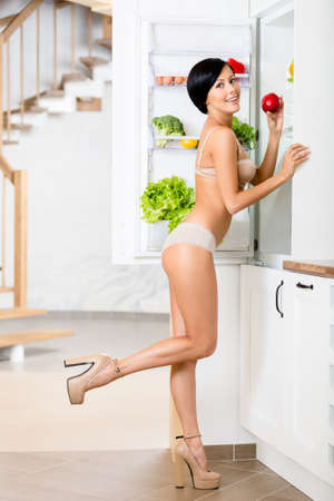 Full-length portrait of woman near the opened refrigerator full of vegetables and fruit. Concept of healthy and dieting food photo