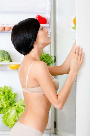niñas en ropa interior: Mujer busca de alimentos en el refrigerador abierto lleno de verduras y frutas. Concepto de comida sana y la dieta
