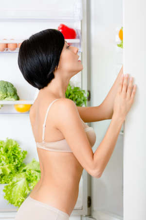 seeks: Woman seeks food in the opened refrigerator full of vegetables and fruit. Concept of healthy and dieting food
