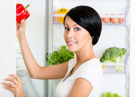 refrigerador: La mujer toma la pimienta dulce del refrigerador abierto lleno de verduras y frutas. Concepto de comida sana y la dieta