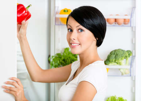 refrigerator with food: Woman takes sweet pepper from the opened refrigerator full of vegetables and fruit. Concept of healthy and dieting food