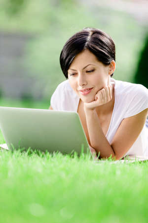 Girl lying on the grass works at the silver laptop. Concept of the online communication photo