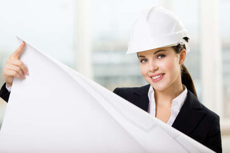 Female engineer in white hard hat hands layout. Concept of successful construction photo