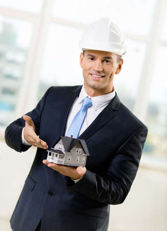 architecting: Engineer in white headpiece pointing at small model house. Concept of real estate