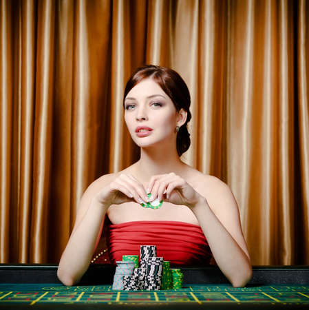 Portrait of female gambler sitting at the roulette table with chip in hand photo