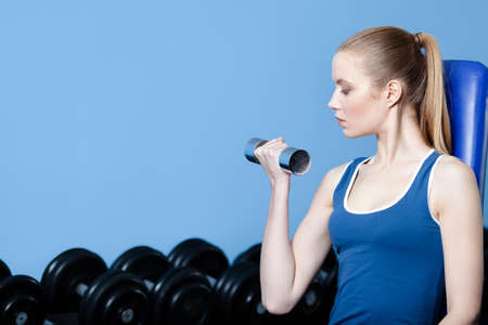 Athletic woman works out with dumbbells in gym photo