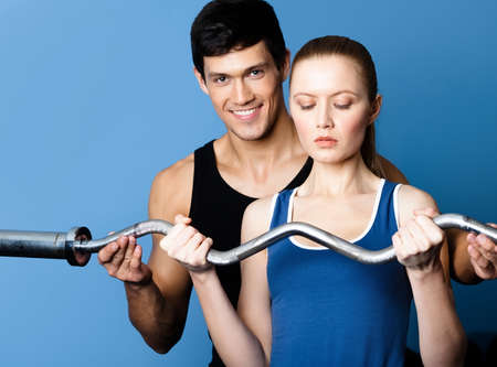 Personal coach shows woman the correct exercise performing with weight Stock Photo - 18074159