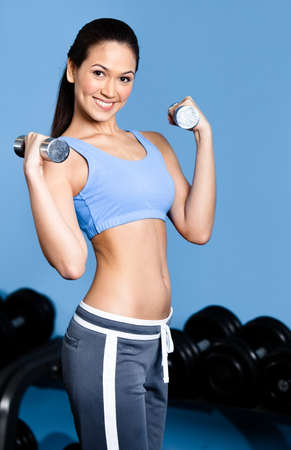 athletic wear: Athletic woman works out with dumbbells in gym class