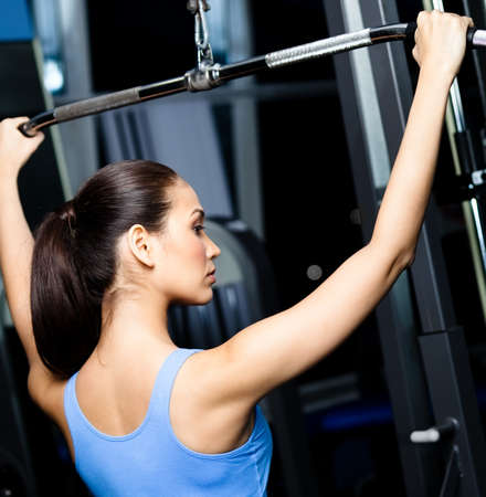 Athletic young woman works out on simulator in gym class Stock Photo - 18076700