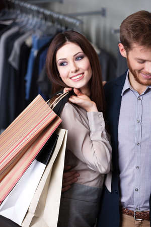 friends shopping: Glad beautiful woman is in the shop with her boyfriend