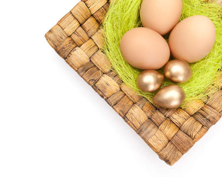 chucky: Brown and golden easter eggs are on wattled plate with sisal green fibre, isolated on a white