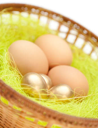 Brown and golden easter eggs are in wattled basket with sisal green fibre, isolated on white background photo