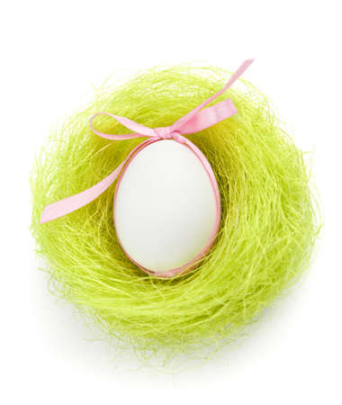 chucky: Egg with pink bow is in the nest of green sisal fibre, isolated on white