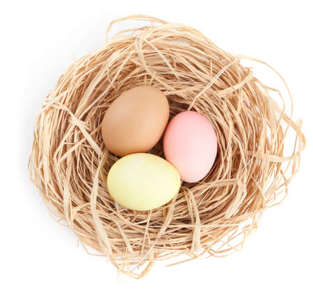 chucky: Three multicolored easter eggs are in the nest, isolated on white Stock Photo