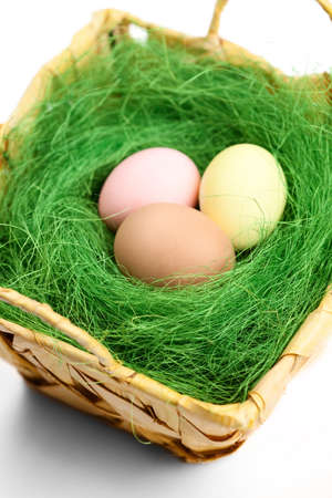 chucky: Multicolored easter eggs are in wattled basket with sisal green fibre, isolated on white Stock Photo