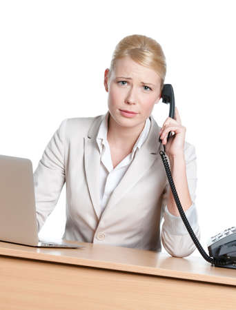 Young business woman sitting at a table and holding phone handset, isolated Stock Photo - 18076577