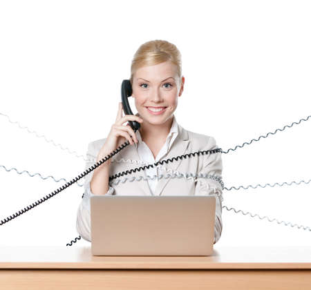 Young businesswoman sitting at a table tied with phone cable, isolated photo