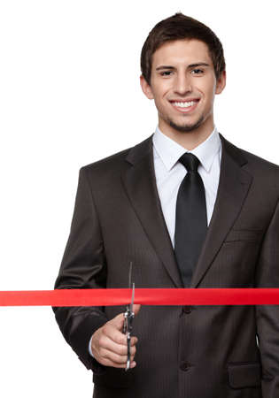 A business man wearing a suit cutting a red ribbon with a pair of scissors. Grand opening ceremony or event, isolated on white photo