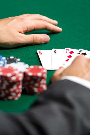 Poker player opens his cards. Risky entertainment of gambling photo