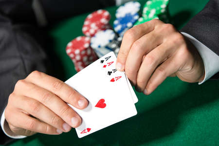 games of chance: Gambler shows poker cards 4 aces. Risky entertainment of gambling