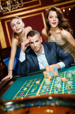 Man with two girls playing roulette at the gambling house. Addiction to the gambling photo