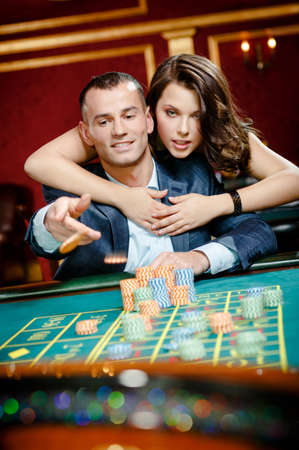 throws: Man embraced by pretty girl throws the chip on the playing table