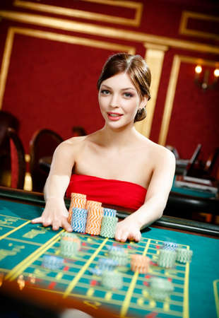 Playing roulette woman stakes at the casino Standard-Bild