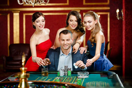 Man surrounded by women plays roulette at the casino photo