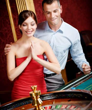 ruleta de casino: Pareja jugando ruleta en el casino gana