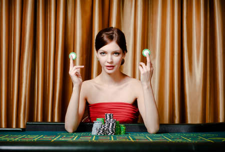 Woman with chips sitting at the roulette table at the casino photo