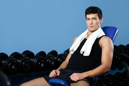 athletic wear: Athletic man rests sitting on blue simulator in gym class Stock Photo