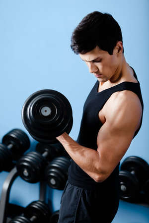 Handsome muscular sportsman uses his dumbbell to exercise flexing bicep muscle photo