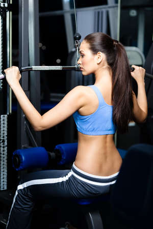 Athletic young woman works out on training apparatus in gym photo