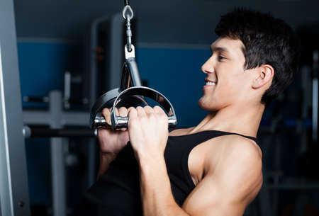 Athletic young man works out on simulator in gym photo