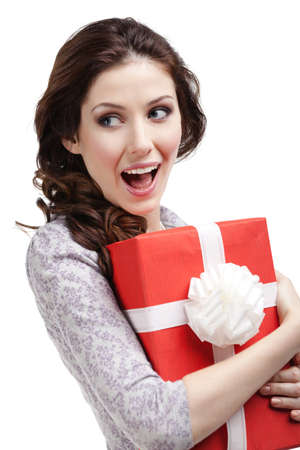 greets: Young woman hands a new years gift wrapped in red paper, isolated on white