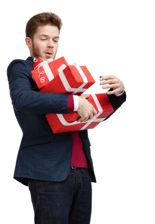 Young man carries a great amount of presents wrapped in red gift paper, isolated on white photo