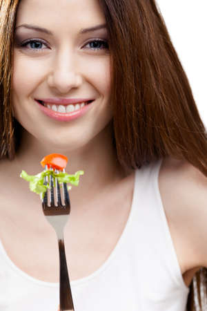 Woman eating fresh salad on a fork, isolated on white photo